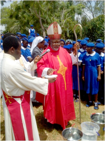 Bishop Avenya blesses water.